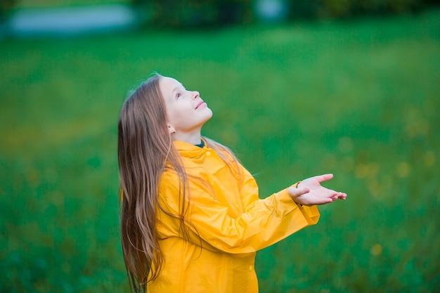 Het meisje geniet van de regen op warme de herfstdag Premium Foto