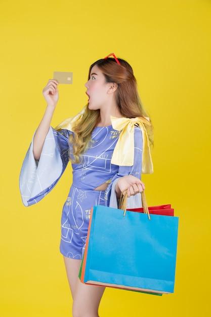 Het meisje heeft een boodschappentas en heeft een smartcard op een gele achtergrond. Gratis Foto