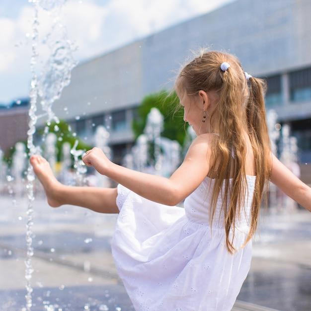 Het meisje heeft plezier in open straatfontein op hete de zomerdag Premium Foto