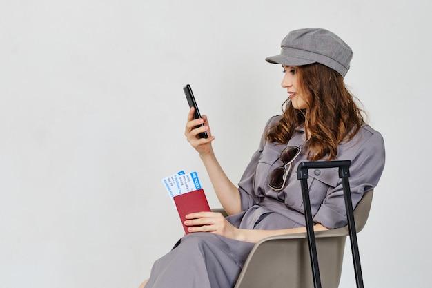 Het meisje heeft vliegtickets met bagage en een paspoort en kijkt naar de smartphone. Premium Foto