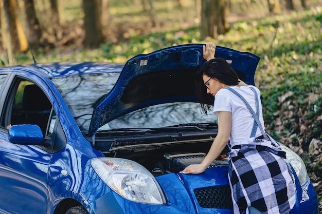 Het meisje herstelt auto met een open kap op weg Premium Foto