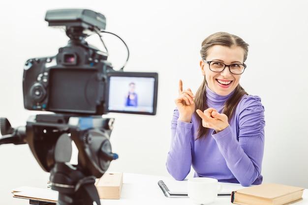 Het meisje houdt een blog-opname bij op de camera. een vrouw met een bril leidt haar vlog Premium Foto