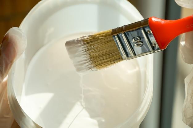 Het meisje houdt een borstel met een rode pen in haar hand en gaat het balkonleuning met witte verf schilderen Premium Foto