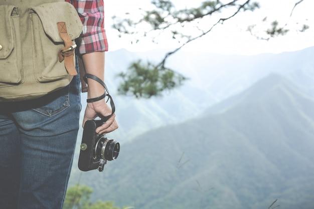 Het meisje houdt een camera vast, wandelt in het tropische bos, samen met rugzakken in het bos, avontuur, reizen, toerisme, klimwandeling. Gratis Foto