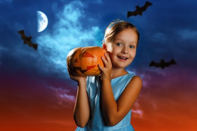 Het meisje houdt een pompoen tegen de achtergrond van de hemel van de avondmaan. Premium Foto