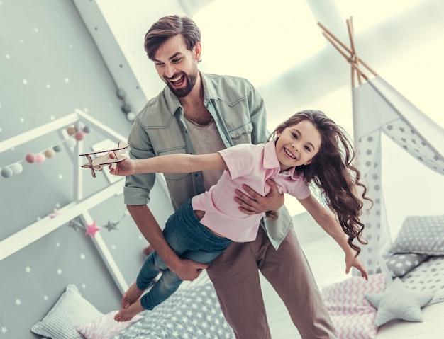 Het meisje houdt een speelgoedvliegtuig en papa houdt zijn dochter vast. Premium Foto