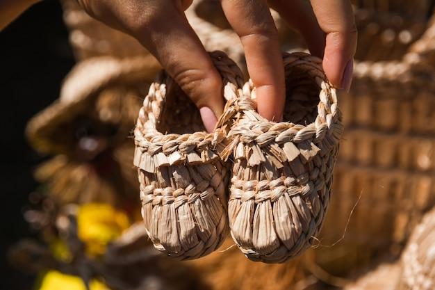 Het meisje houdt in haar handen souvenir handgemaakte kinderschoenen gemaakt van stro voor festivals van volkskunst en ambachten Premium Foto