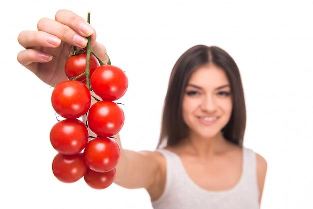 Het meisje houdt tomaten in handen en glimlacht. Premium Foto