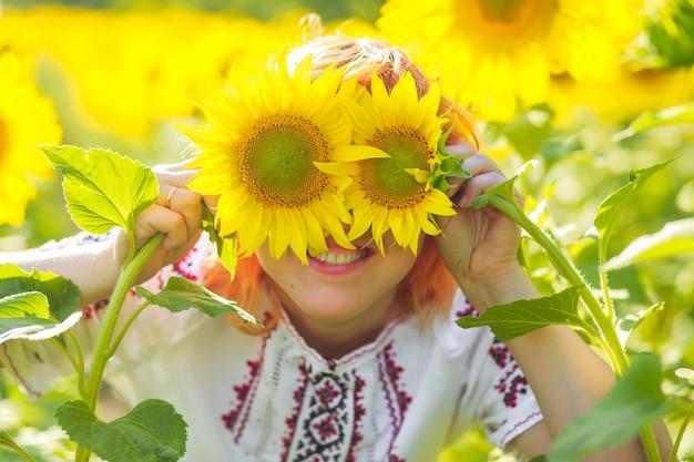 Het meisje in borduurwerk verborg ogen achter zonnebloemen Premium Foto