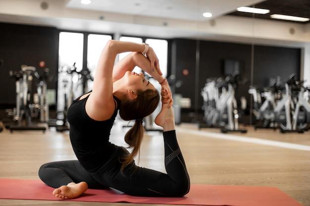 Het meisje in de sportschool doet yoga om zichzelf in vorm te houden of overgewicht te beheersen. Premium Foto