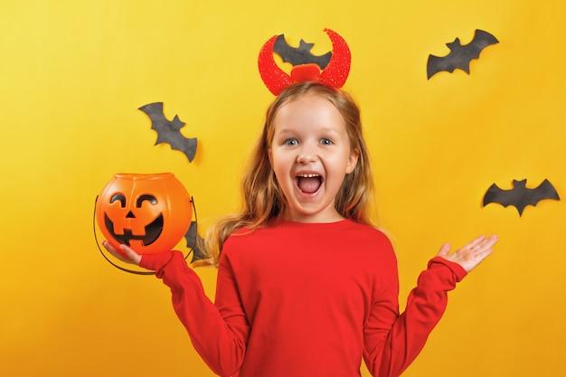 Het meisje in een duivelskostuum houdt een emmer pompoen Premium Foto