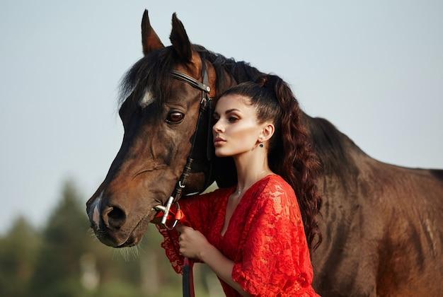 Het meisje in een lange kleding bevindt zich dichtbij een paard, een mooie vrouw strijkt een paard en houdt het teugel in een gebied in de herfst Premium Foto