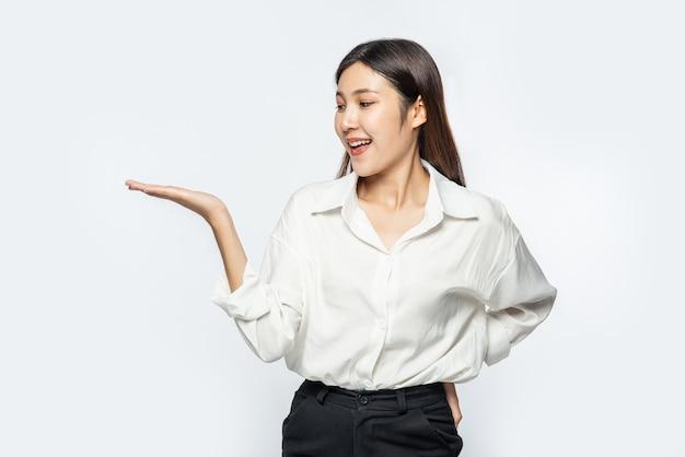 Het meisje in een wit overhemd houdt iets vast Gratis Foto