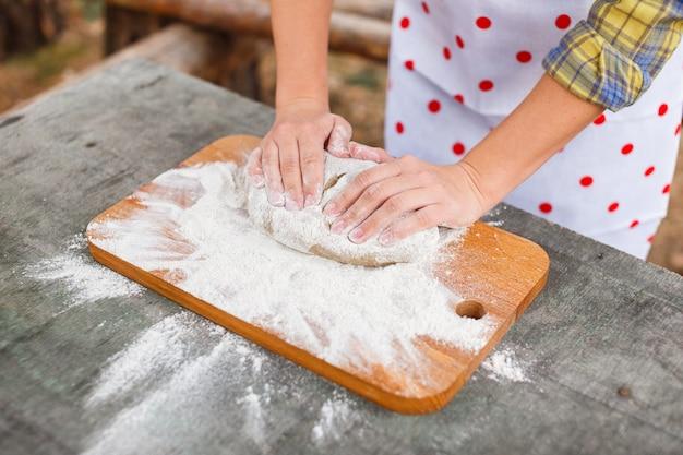 Het meisje in een witte schort bereidt het deeg op een snijplank Premium Foto
