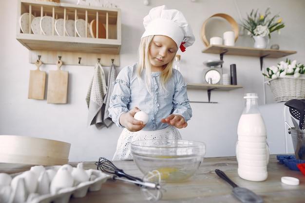 Het meisje in een witte shefhoed kookt het deeg voor koekjes Gratis Foto