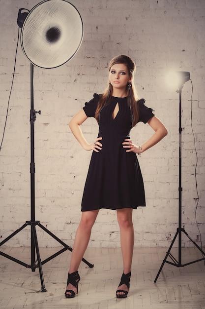Het meisje in een zwarte kleding bevindt zich in studio op witte bakstenen muurachtergrond Premium Foto