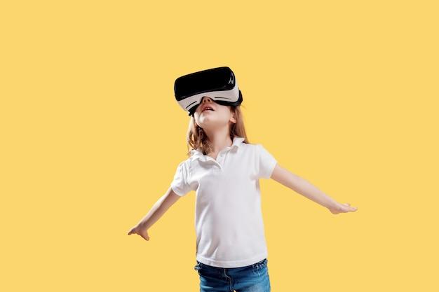 Het meisje in formele uitrusting die vr-glazen het zetten dragen deelt in geïsoleerde opwinding uit. kind gebruikt een gaminggadget voor virtual reality. virtuele technologie Premium Foto
