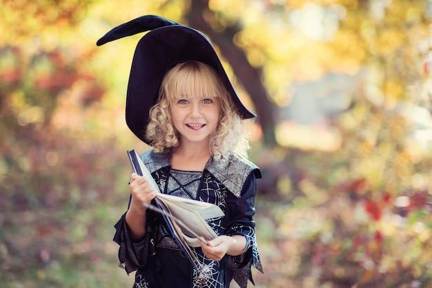 Het meisje in heksenkostuum viert halloween openlucht en heeft pret. Premium Foto