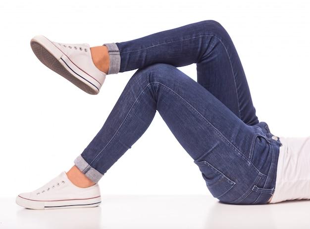 Het meisje in jeans ligt op een witte vloer. Premium Foto