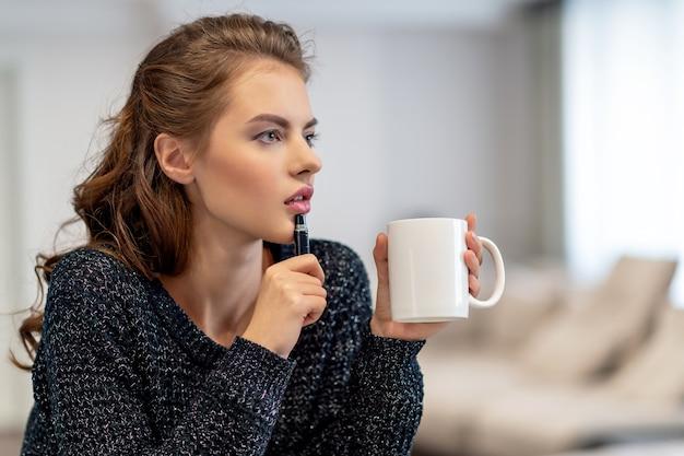Het meisje is thuis. vrouw alleen in haar kamer. ze zit op de tafel en schrijft met het potlood iets in haar notitieboekje Gratis Foto