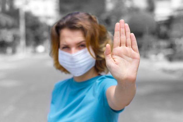 Het meisje, jonge vrouw in beschermend steriel medisch masker op haar gezicht in openlucht, op aziatische straat toont palm, hand, houdt geen teken tegen. luchtvervuiling, virus, chinees pandemisch coronavirusconcept. focus op de hand. Premium Foto