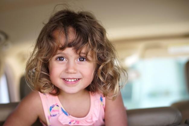 Het meisje kijkt gelukkig in de auto Premium Foto