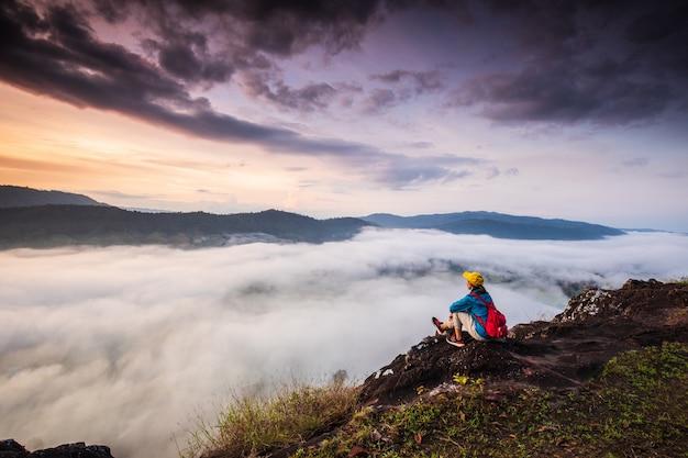 Het meisje kijkt naar de mistige zee op de hoge berg. Premium Foto