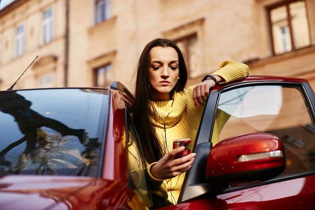 Het meisje kijkt naar de telefoon en gaat in de auto zitten Gratis Foto
