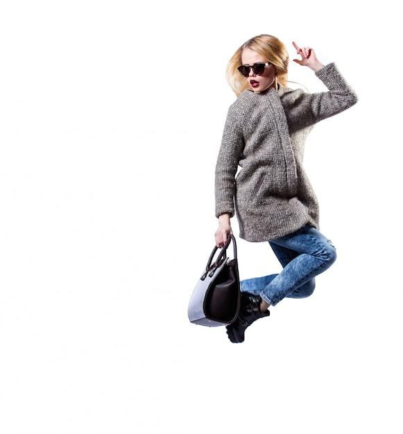 Het meisje kleedde zich in grijze bontjas, dragend zonnebril en zwarte zak, die op witte achtergrond stellen. sexy schoonheid mode blond. Premium Foto