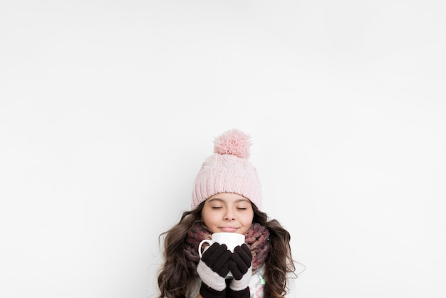 Het meisje kleedde zich warm met een kop in handen Gratis Foto