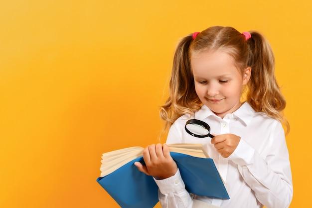 Het meisje leest een boek op de lijst met een vergrootglas op een gele achtergrond. Premium Foto