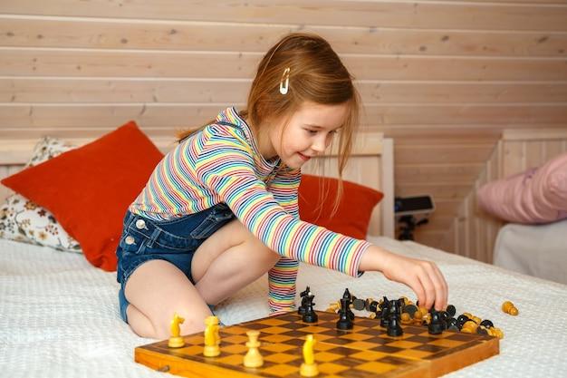 Het meisje legt stukken op een schaakbord. schaakspel Premium Foto