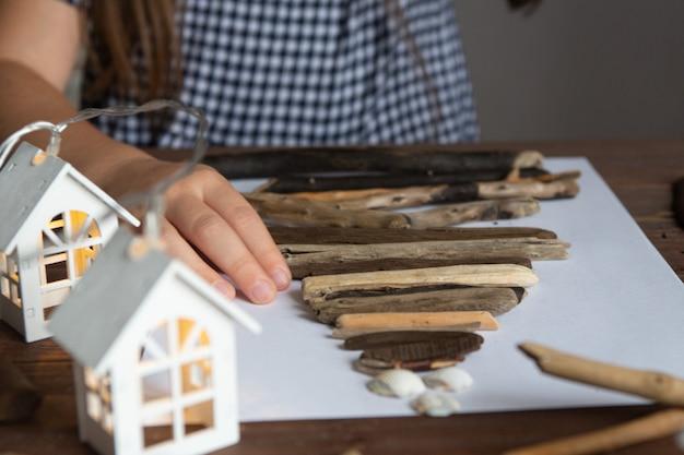 Het meisje maakt een kerstboomambacht van stokken en schelpencreativiteit Premium Foto