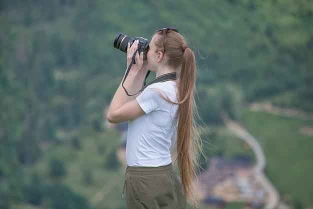 Het meisje met camera bevindt zich een heuvel en het fotograferen van aard. bos aan Premium Foto