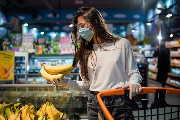 Het meisje met chirurgisch masker gaat bananen kopen. Gratis Foto