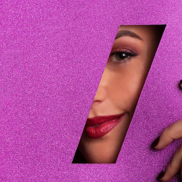 Het meisje met helder maakt omhoog, rode lippenstift kijkend door gat in violet pape Premium Foto