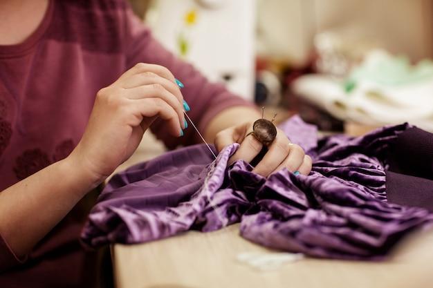 Het meisje naait een jurk, handen van dichtbij Premium Foto
