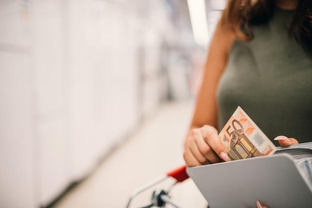 Het meisje neemt een bankbiljet van vijftig euro van portefeuille. detailopname. Premium Foto