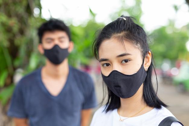 Het meisje op straat draagt een gezichtsmasker om het virus te voorkomen en waas te weerstaan. Gratis Foto