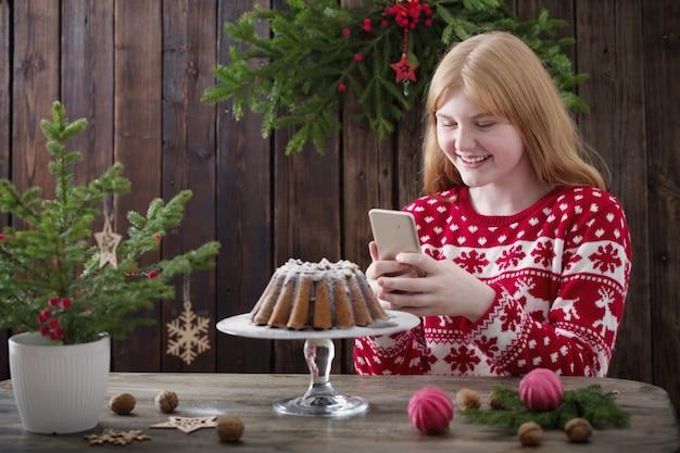 Het meisje schiet kerstmiscake op mobiele telefooncamera Premium Foto
