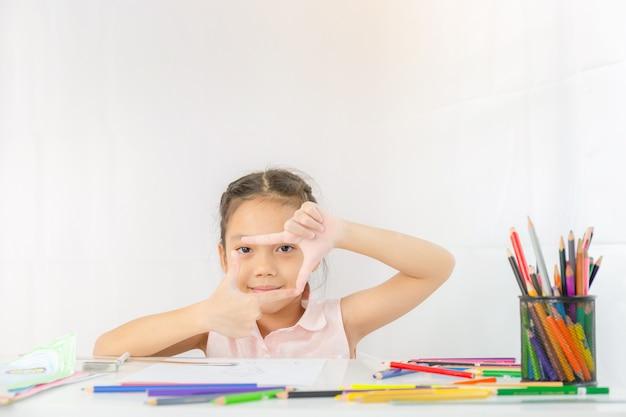 Het meisje toont een kader van handen zoals foto, jong geitjetekening met kleurrijke potloden Premium Foto