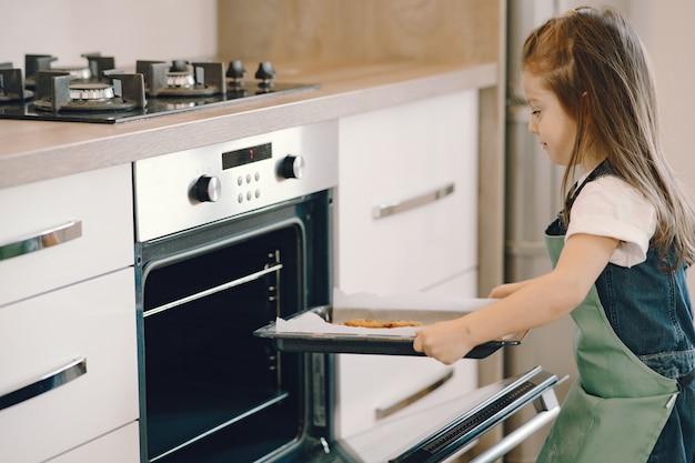 Het meisje trekt een koekjesdienblad uit de oven Gratis Foto