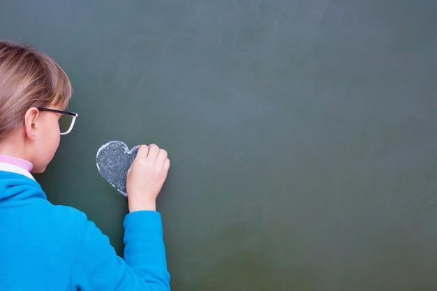 Het meisje trekt hart een krijt op een schoolbord Premium Foto
