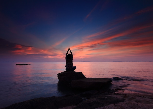 Het meisje van de silhouetyoga bij de strandzonsondergang Premium Foto