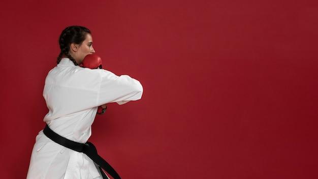 Het meisje van de vechtsportenkarate met zwarte band en exemplaar ruimteachtergrond Gratis Foto