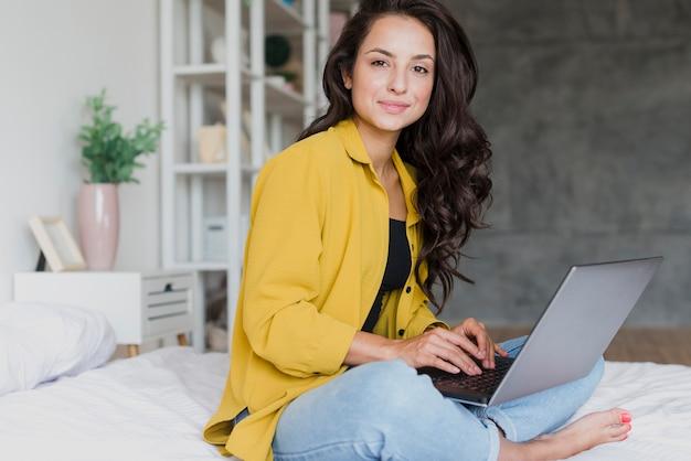 Het meisje van zijaanzichtsmiley met binnen laptop Gratis Foto