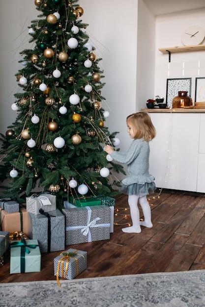 Het meisje verfraait binnen de kerstboom Premium Foto