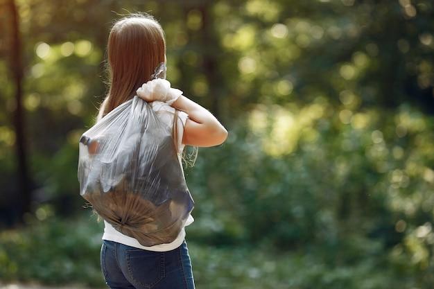 Het meisje verzamelt afval in vuilniszakken in park Gratis Foto