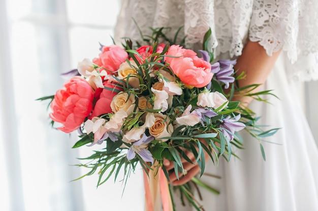 Het meisje verzamelt een boeket van prachtige bloemen: roos, pioenroos, lila, narcis Premium Foto