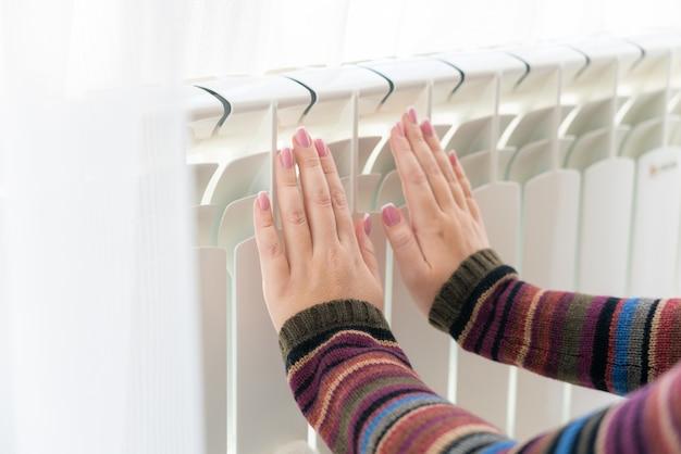 Het meisje warmt de bevroren handen boven hete radiator op, sluit mening Premium Foto
